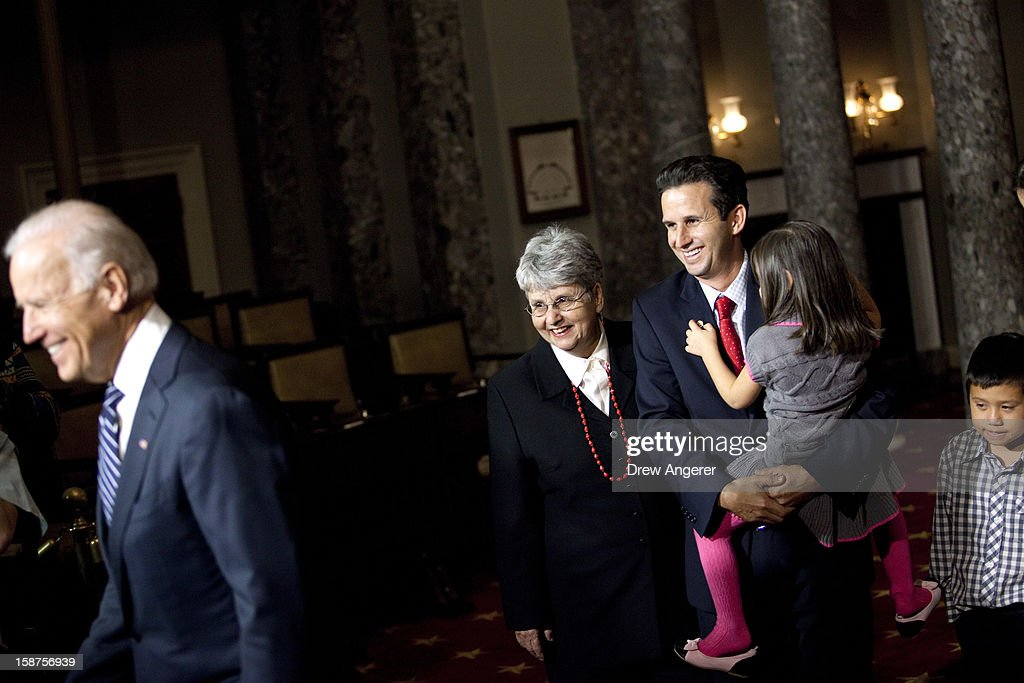 Flanked by his mother Barbara Schatz (2L) and son Tyler Schatz (R), Sen. Brian Schatz (D-HI) (C) holds his daughter Mia Schatz (2R) during in a ceremonial swearing in event with Vice President Joe Biden, in the Old Senate Chamber on Capitol Hill, on December 27, 2012 in Washington, DC. Schatz is filling the late Sen. Daniel Inouye's (D-HI) seat in the Senate.