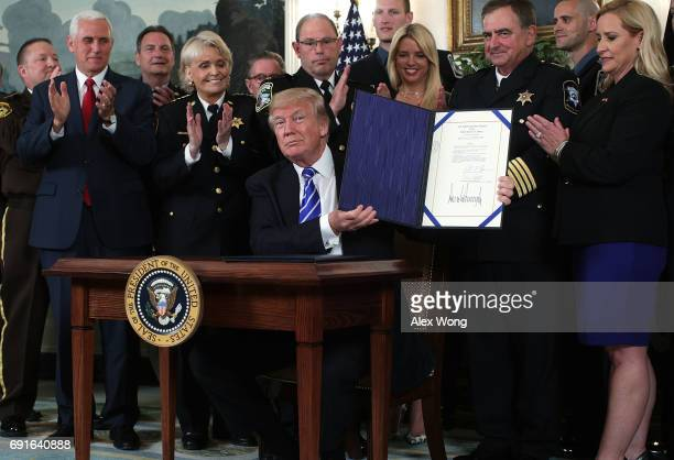 Flanked by law enforcement officials and Vice President Mike Pence US President Donald Trump shows the bill he has signed during a bill signing in...