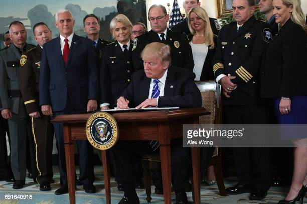 Flanked by law enforcement officials and Vice President Mike Pence US President Donald Trump participates in a bill signing in the Diplomatic...