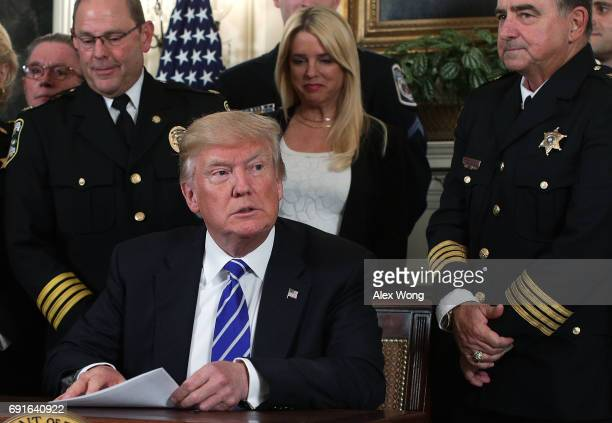Flanked by law enforcement officials US President Donald Trump participates in a bill signing in the Diplomatic Reception Room of the White House...