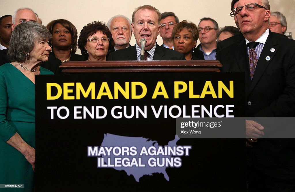 Flanked by mayors and gun control activists, Chief Policy Advisor to New York City Mayor Michael Bloomberg and Chairman of Mayors Against Illegal Guns John Feinblatt (C) speaks during a news conference January 16, 2013 on Capitol Hill in Washington, DC. Members of Mayors Against Illegal Guns held a news conference to call on Congress to take action to end gun violence.