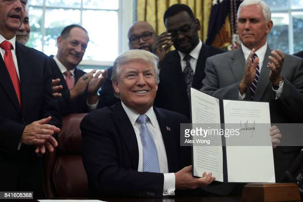 Flanked by Vice President Mike Pence and faith leaders US President Donald Trump signs a proclamation in the Oval Office of the White House September...