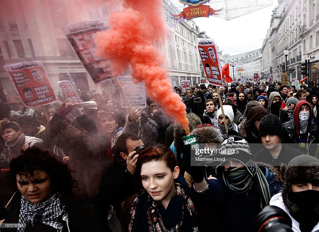 A flare emits smoke as students take part in a protest over the Government's budget cuts and proposed rise in tuition fees on November 30, 2010 in London, England. Hundreds of students evaded police containment tactics and marched throughout Westminster and the City of London from Trafalgar Square in the third major protest of its kind in London in as many weeks.