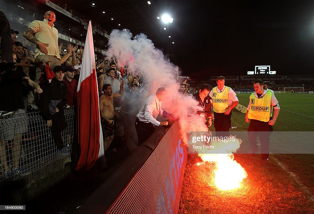 A flare from Wanderers fans is thrown into a bucket by security during the round 27 A-League match between the Newcastle Jets and Western Sydney at Hunter Stadium on March 29, 2013 in Newcastle, Australia.