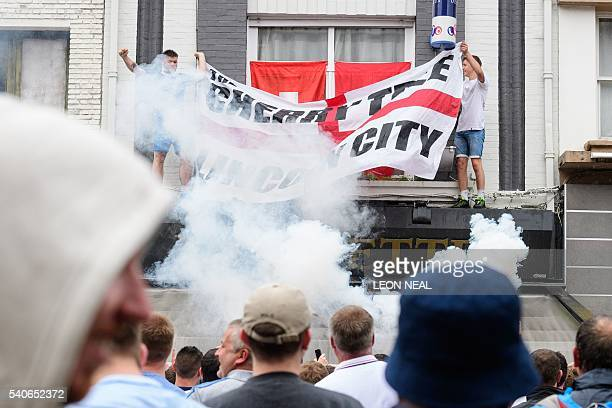 A flare is ignited as England fans hang a flag onto a bar's canopy in central Lens on 16 June 2016 on the day that England plays Wales during the...
