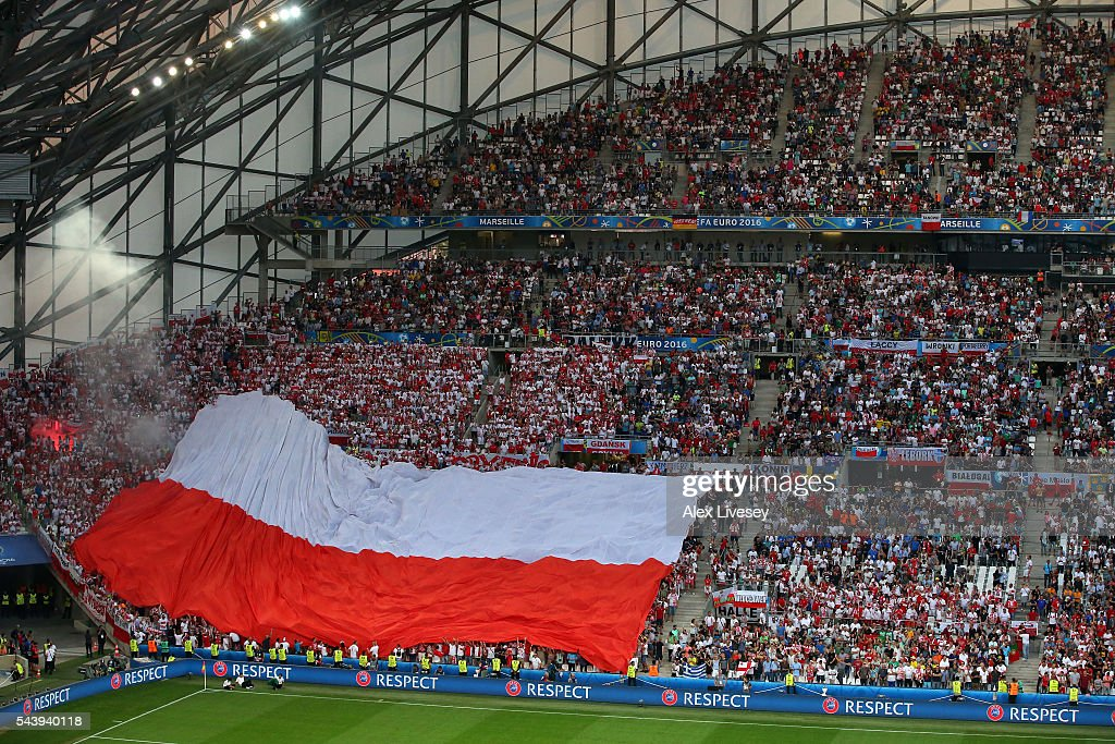 A flare is seen next to a big Poland national flag in the stand prior to the UEFA EURO 2016 quarter final match between Poland and Portugal at Stade Velodrome on June 30, 2016 in Marseille, France.