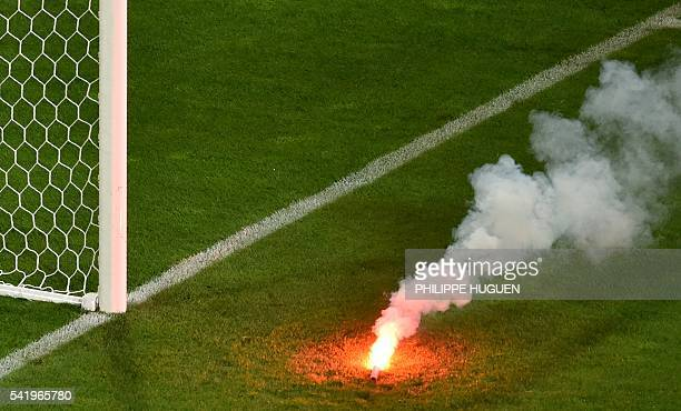 A flare is seen on the pitch during the Euro 2016 group D football match between Czech Republic and Turkey at BollaertDelelis stadium in Lens on June...