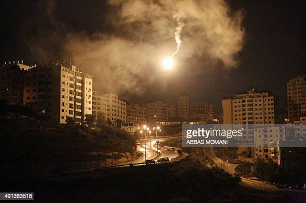A flare lights up the sky as Palestinian youths clash with Israeli security forces in the town of Surda the hometown of Palestinian Mohannad Shafiq...