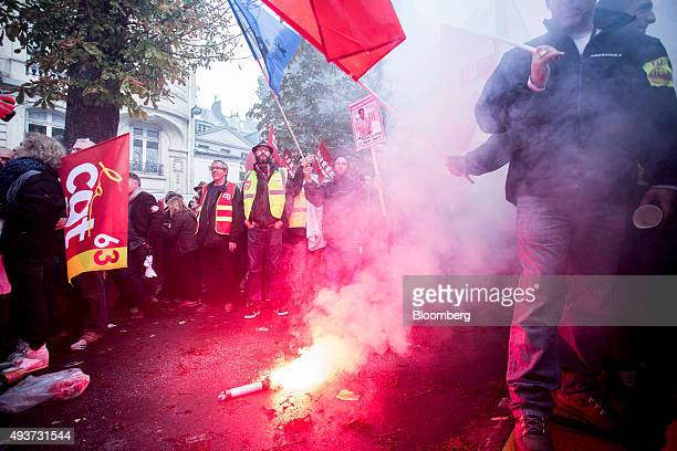 A flare releases smoke as it burns on the ground while employees from the Air France division of Air FranceKLM Group gather for a protest by union...
