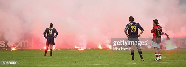 Flares rain down onto the pitch from Inter Milan fans as Juan Sebastian Veron and Marco Materazzi of Inter Milan and Rui Costa of AC Milan look on...