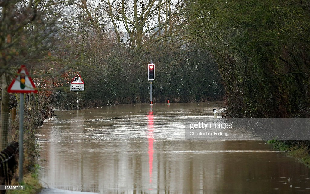 A flash flood makes a road impassable near Tewkesbury at the confluence of the River Severn and the River Avon on December 24, 2012 in Tewkesbury, England. Forecasters have predicted more rain to sweep across the country causing flash flooding over the coming days. The South West of England has been badly affected causing major disruption to the rail network delaying journeys for people making their way home for Christmas.