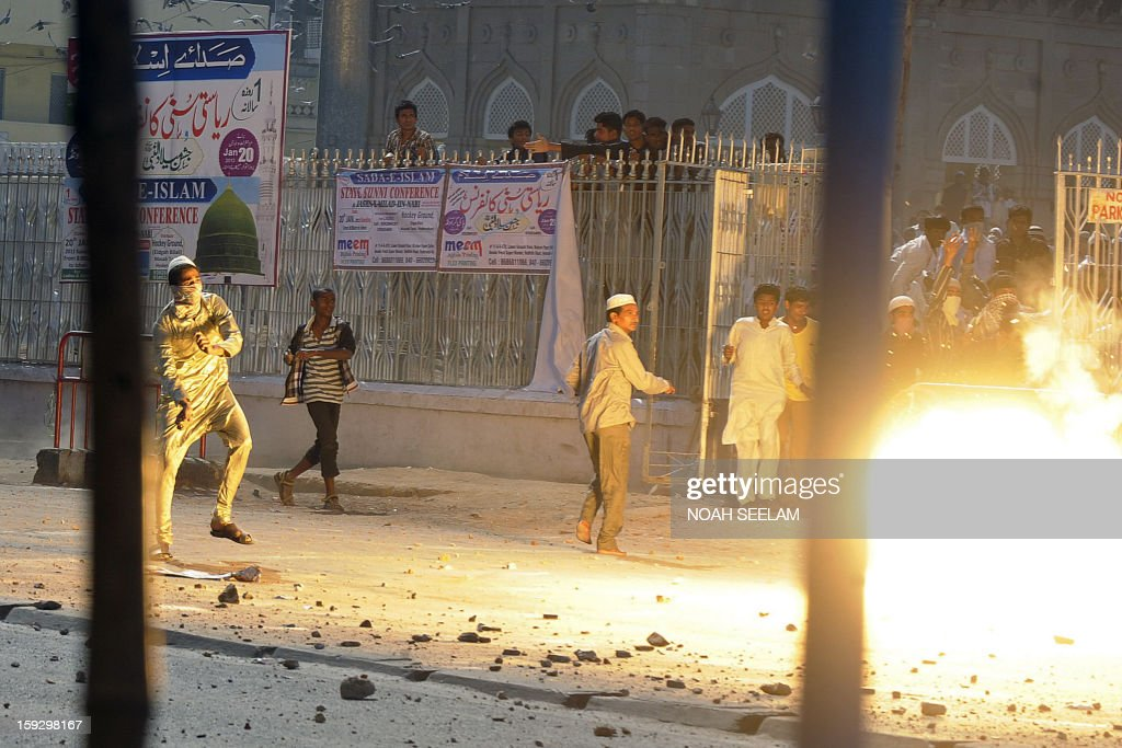 A flash from a tear gas shell is seen as supporters of the Majlis-e-Ittehadul Muslimeen (MIM) clash with police outside the historic Mecca Masjid following congregational Friday prayers in Hyderabad on January 11, 2013. Demonstrators took to the streets following the arrest of Majlis-e-Ittehadul Muslimeen (MIM) leader Akbaruddin Owaisi for allegedly making hate speeches. AFP PHOTO/Noah SEELAM