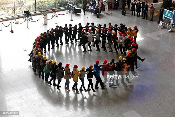A flash mob made of train staff and volunteers dances during the fisrt day of spring rush at Zhengzhou Railway Station on February 4 2015 in...