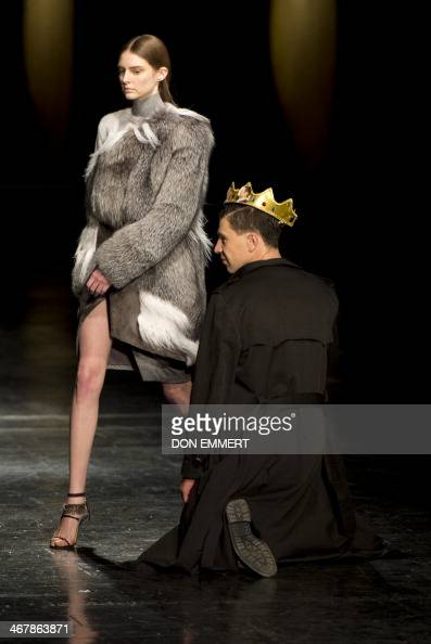 A flasher kneels in front of a model wearING designs by Prabal Gurung during the MercedesBenz Fashion Week Fall/Winter 2014 shows ON February 8 2014...