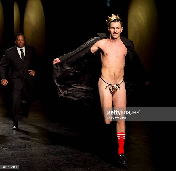 A flasher runs from security guards during as show of designs by Prabal Gurung during the MercedesBenz Fashion Week Fall/Winter 2014 shows on...