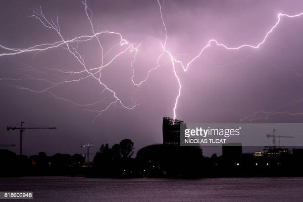 TOPSHOT Flashes of lightning strike 'La Cite du Vin' in Bordeaux southwestern France during a thunderstorm on July 18 2017 / AFP PHOTO / NICOLAS TUCAT