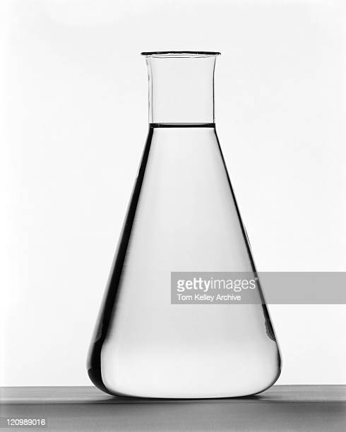 Flask filled with water on white background, close-up