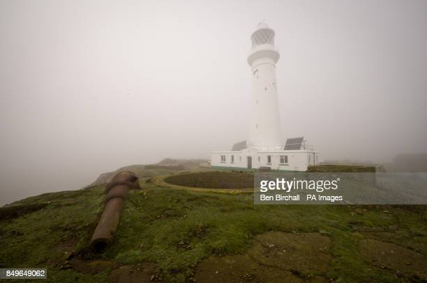 Flat Holm Lighthouse is seen through dense fog with one of the old Victorian gun emplacements in the foreground complete with Moncrieff pit...