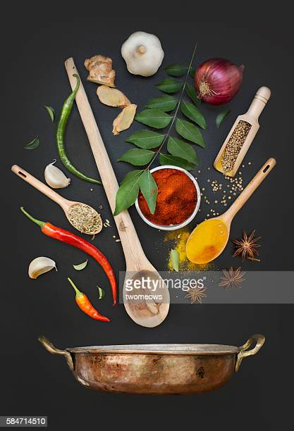 Flat lay asian or indian cuisine recipe ingredient herb and spices on black texture background.