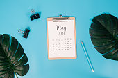 Flat lay calendar with clipboard, palm leaves and pencil on blue background. May 2019. top view.