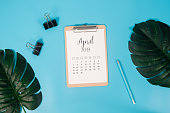 Flat lay calendar with clipboard, palm leaves and pencil on blue background. April 2019. top view.