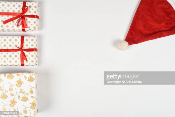 Flat lay Christmas gift boxes, Santa cap on white table with copy space