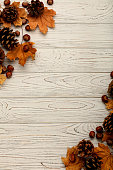 Flat lay frame of autumn leaves, cones and nuts on a wooden background. Selective focus.