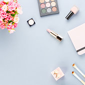 Flat lay home office desk. Feminine workspace with planner, pink flowers bouquet, cosmetics and fashion accessories on grey background. Fashion or beauty blogger concept.