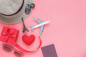 Flat lay image of accessory clothing man or women to plan travel in valentines day background concept.Passport & clothes with many items in holiday season.Table top view several object on pink paper.