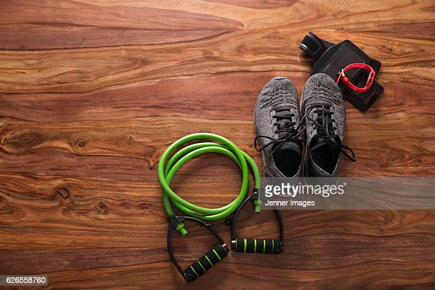 Flat Lay image of fitness equipment on wooden floor.