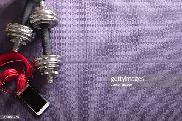Flat Lay image of weights and smartphone on fitness mat.