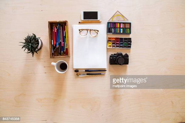 Flat lay of camera, smart phone, coffee cup, crayons, chalks and paints on wooden table.