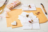 Girl baptism and event invitations preparation.  Flat lay of gift box and invitations on a white wooden tabletop, background.