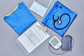 Directly above flat lay shot of medical supplies. Scrubs are placed with application form blood pressure gauge stethoscope and surgical mask. All are on gray background.