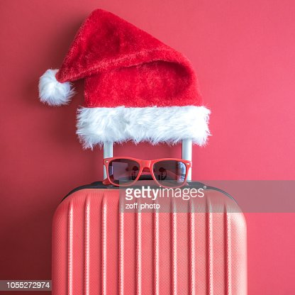 Flat lay of Santa Claus hat, sunglasses and luggage abstract isolated on red. : Foto stock