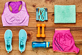 Directly above flat lay shot of sports equipment arranged on hardwood floor. Dumbbells are surrounded with sports clothing  water bottle  towel and shoes on wood. All are representing healthy lifestyl