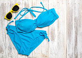 Flat lay of summer items with colorful bikini and accessories on white wooden background, Summer concept, Copy space