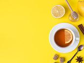 Flat lay on the yellow bright background Black tea Lemon Cinnamon Star Anise brown sugar jar of Honey.