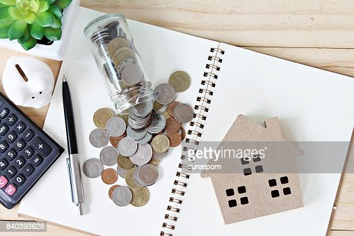 Flat lay or top view of wood house model and coins scattered from glass jar on open blank notebook paper : Stock Photo