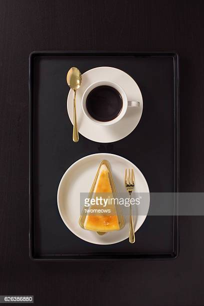 Flat lay overhead view black coffee and cheese cake on black background.