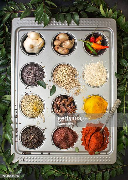 Flat lay overhead view herb and spices in tray on textured black background.