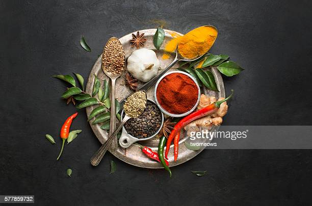 Flat lay overhead view herb and spices on textured black background.