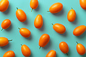 Flat lay pattern of fresh kumquats on a colorful background. Top view