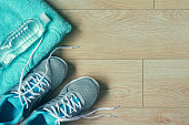 Flat lay photo of sports equipment sneakers,towel,bottle of water, top view, toned image over wooden background with copy space