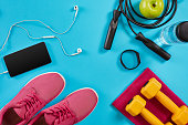 Flat lay shot of sneakers, jumping rope, dumbbells and smartphone on blue background. Active lifestyle, body care concept. Top view. Copy space. Flat lay. Still life