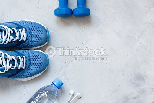 Flat lay sport shoes, bottle of water, dumbbells and earphones