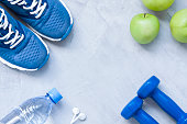 Flat lay sport shoes, dumbbells, earphones, apples, bottle of water on gray concrete .background. Concept healthy lifestyle, sport and diet. Selective focus. Flat lay shot of .Sport equipment.