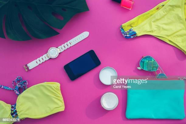 flat lay summer bag with feminine beauty items
