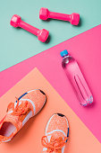 Flat lay with sneakers, dumbbells and sport bottle on colorful background