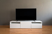 Flat LCD television on white cabinet in the living room with dark gray wall and parquet floor